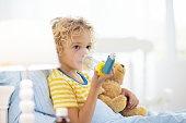 Sick little boy with asthma medicine. Ill child.