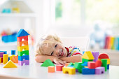 Kids toys. Child building tower of toy blocks.