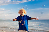 Kids blow bubble at beach. Child with bubbles