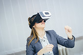 Beautiful and elegant woman in a suit using the virtual reality headset and have fun indoor.