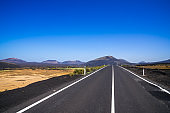 Spain, Lanzarote, Black asphalt road alongside pretty volcanic nature landscapes and volcanoes