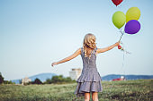 Young woman with balloons in a park