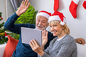 Senior couple using tablet to video phone call to greeting their family for Christmas festival, wave hand, sitting on sofa with decoration and tree