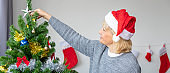 Caucasian senior couple elderly woman decorating Christmas tree for holiday festival