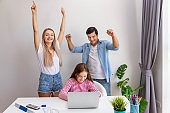 Parent father and mother watching and teaching daughter to use notebook computer at home, raise hand with cheerful