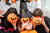 Happy cute children boy and girls in costume on sofa in living room during Halloween party, with  pumpkin Jack-o'-lantern cover face