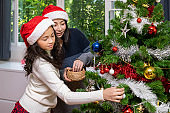 Mother and daughter are decorating Christmas tree together for the festival, in living room