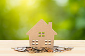 Model house over coin money pile on wooden desk on green tree background, mortgage concept