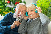 Senior couple man and woman singing song Christmas carol together, sitting on sofa with tree and decoration in background