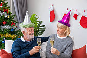 Senior couple man and woman with champagne and chatting, sitting on sofa with Christmas tree and decoration in background