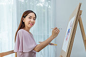 Woman female artist painting picture at home as her hobby, looking at camera