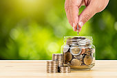 Coin glass jar container and stack on wooden desk, on green tree background, with hand putting money, retirement saving concept,
