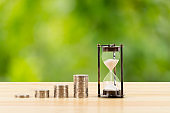 Coin stack and hourglass on wooden desk  on green tree background, time for saving concept