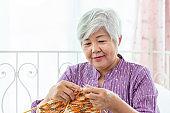 Happy senior woman female knitting at home as hobby