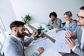 Multi ethnic group of architects working on plans in board room