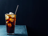 Cold brew coffee in a glass with metal straw on a dark background.