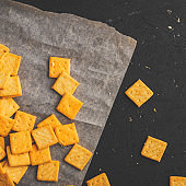 Salty square crackers on a paper and dark concrete background