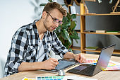 Young adult man working with graphic tablet in office