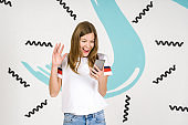 Young beautiful woman standing on white art background with smartphone in hand, waving hello in camera