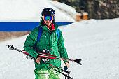 Professional athlete skier holding skis.