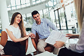 Financial advisor showing report to young couple for their investment