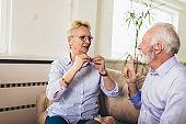 Smiling senior woman talking using sign language with her hearing impairment man