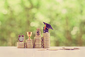 School funding, saving for higher education concept : Black graduation cap, campus diploma, US dollar bag, trophy cup of success or winner reward, a clock on rising coins, depicts passage of success