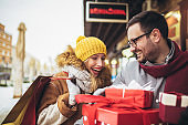 Young couple doing Christmas shopping in the city