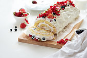 Sponge (biscuit) cake roll filling whipped cream and berries decorated strawberry, blueberry and red currants on white wooden background. Soft focus. Summer food concept