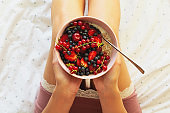 Healthy summer breakfast in the bed. Woman eating oatmeal porridge with berries. Healthy eating concept. Top view