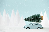 Retro car toy carrying Christmas fir tree in snowy landscape. Christmas or New Year celebration concept. Copy space. Selective focus