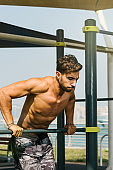 Portrait of a young arab sports man exercising with push ups exercise on horizontal baroutdoors in Dubai during summer time.