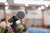 Seminar Conference Concept : Close-up Microphones on abstract blurred of speech in conference meeting room, front speaking blur bokeh light in event convention hall in hotel background