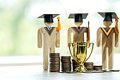 Education graduation in achievement success concept: golden trophy winner with rising money coins with Students university models, management study competition leadership and inspiration in life