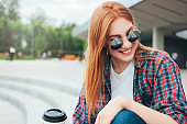 Attractive redhead smiling girl in round sunglasses with cup of coffee to go in hands in casual clothes sitting on street in city