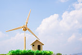 Wind mill of Eco Green Energy/Future Alternative energy or awareness of environment concept,Wind turbine/ home on grass blue sky background. Idea on sustainable residential house use ecology renewable