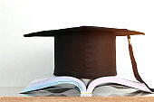 Education of knowledge learning study abroad international Ideas. Graduation hat on open textbook on wooden desk in library archive room, Concept of reading book bring success degree in life
