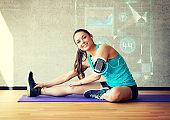 smiling woman stretching leg on mat in gym