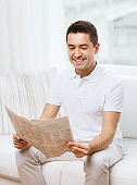 happy man reading newspaper at home