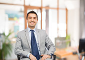happy businessman sitting in office chair
