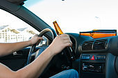 Car driver holding a bottle of beer