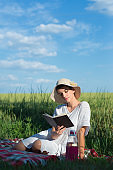 Young woman reading book in the summer nature