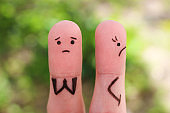 Fingers art of displeased couple. Woman was offended, man asks her forgiveness.