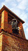 ancient medieval brick bell tower with bronze bell and blue sky
