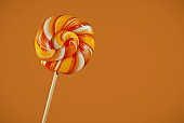 Multicolored candies on a wooden stick. Yellow, orange and green lollipops isolated on bright background.
