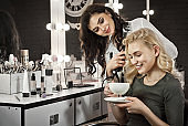 The girl drinks coffee in a beauty salon. The wizard makes a hairstyle to the client. Blonde and brunette against the backdrop of a mirror with a backlight. Delicate customer service.