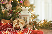 Christmas decoration background with leaves and pine cones, red scarf, white lantern, gift box and star shape blinker on wood table with copy space. Bokeh Christmas tree wallpaper for xmas celebration