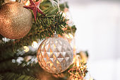 Sweet Christmas decor ball, golden glitter ball and red star hanging on Christmas tree with copy space in close up concept for background. Beautiful bokeh or blurred wallpaper for xmas celebration.