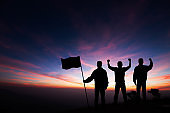 Silhouette of three young men standing on top of the mountain with fists raised up and holding flag on sunrise background, success, achievement,victory and winning concept