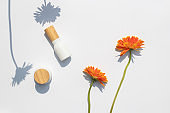 Top view of white cosmetic bottle containers with Gerbera flowers and with shadow of flower on white background.